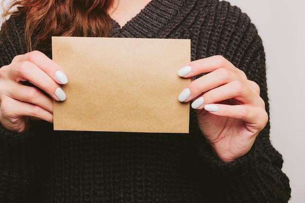 Девушка в свитере держит пустую карточку из бумаги формата а5. презентация. белый маникюр Premium Фотографии