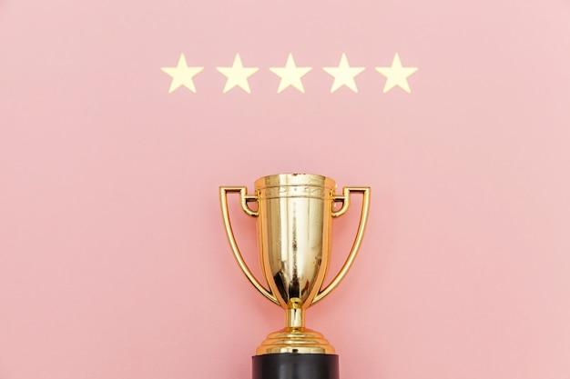 Просто плоский дизайн победителя или чемпионский золотой кубок и рейтинг 5 звезд на розовом фоне. победа первое место соревнований. концепция победы или успеха. вид сверху копией пространства. Premium Фотографии