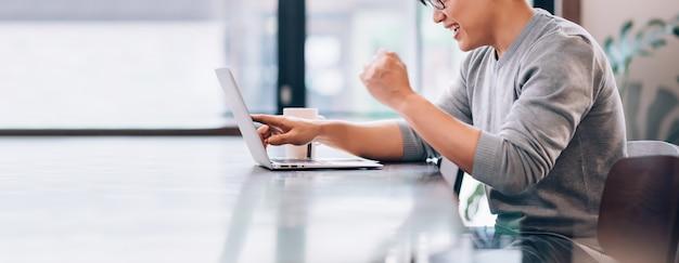 Азиатский мужчина с помощью портативного компьютера подключается к высокоскоростному интернету технология беспроводной связи 5g работа на дому Premium Фотографии