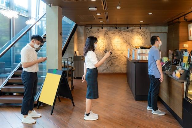 他の人から6フィートのマスク立ち距離を身に着けているアジア人3人は、covid-19ウイルスやコーヒーカフェでの感染リスクのために社会的距離を隔てている人々から距離を守っています。 Premium写真