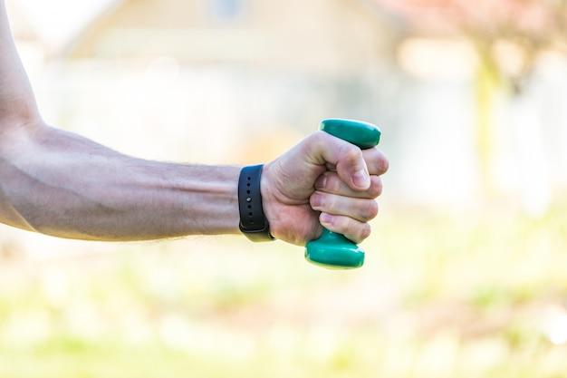 男の手がプラスチック製のスポーツダンベルを持っています。 60年後のスポーツ活動。健康的なライフスタイルのコンセプトです。 Premium写真