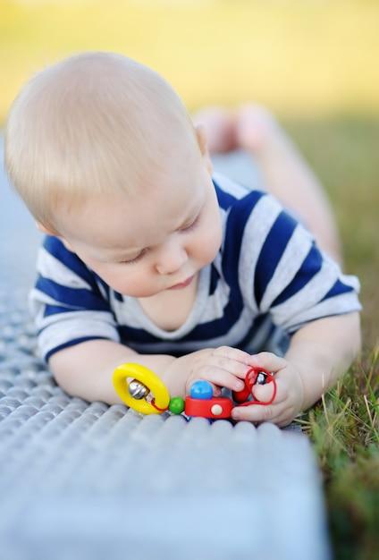 明るいおもちゃで遊ぶ6ヶ月歳の赤ちゃんの屋外のポートレート Premium写真