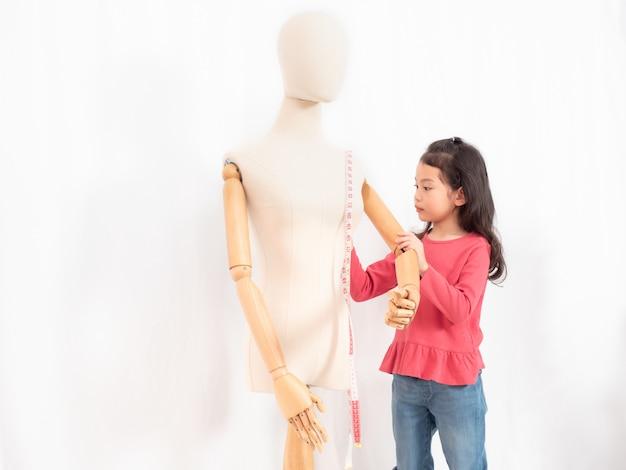 マネキンで仕立て屋やデザイナーの職業をしているアジアのかわいい女の子6歳の役割 Premium写真