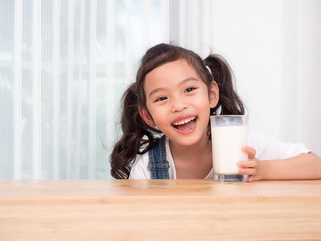 ガラスから牛乳を飲む幸せなかわいい女の子6歳。 Premium写真