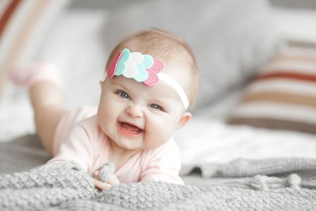 Милый маленький ребенок дома в спальне. младенец в помещении. 6-месячный детский портрет. очаровательны милая девочка. Premium Фотографии