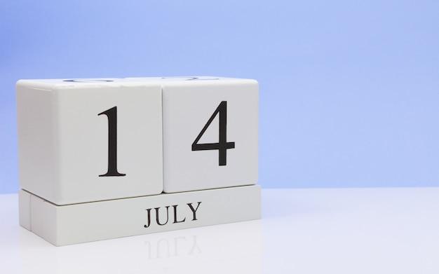 7月14日月の14日、反射、明るい青の背景を持つ白いテーブルに毎日のカレンダー。 Premium写真