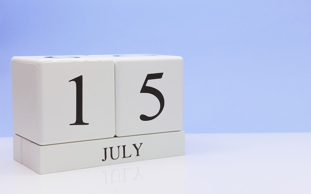 7月15日月の15日、反射、明るい青の背景を持つ白いテーブルに毎日のカレンダー。 Premium写真