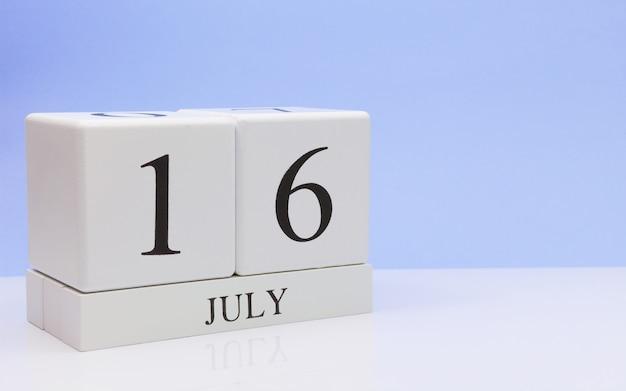 7月16日月の16日、反射、明るい青の背景を持つ白いテーブルに毎日のカレンダー。夏時間、テキスト用の空きスペース Premium写真