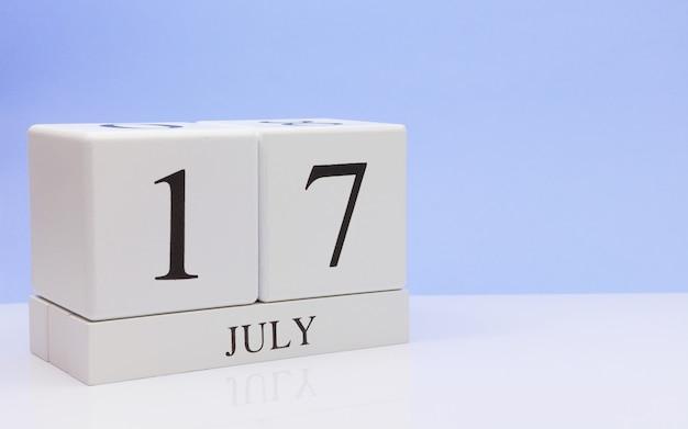 7月17日月の17日目、明るい青の背景と、反射と白いテーブルに毎日のカレンダー。 Premium写真