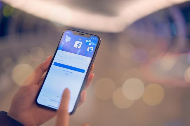 Бангкок, таиланд - 7 октября 2019 года: рука нажимает на экран facebook на apple iphone, социальные сети используют для обмена информацией и создания сетей. Premium Фотографии