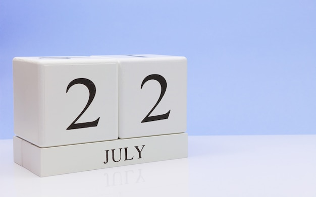 7月22日月の22日、明るい青の背景を持つ、反射と白いテーブルに毎日のカレンダー。 Premium写真