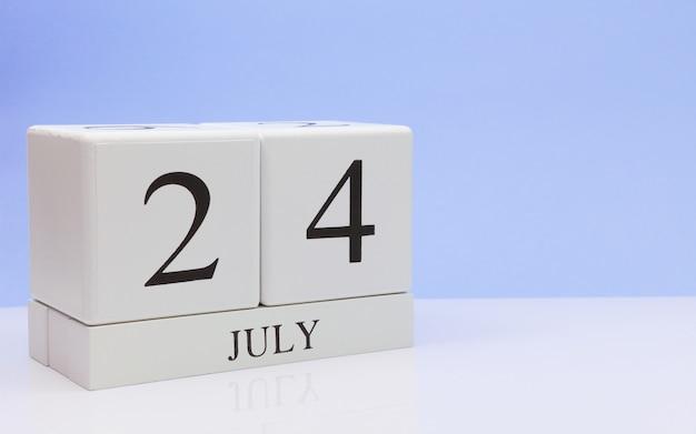 7月24日月の24日、明るい青の背景に、反射と白いテーブルに毎日のカレンダー。 Premium写真