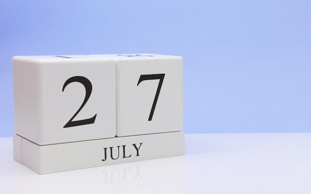 7月27日月の27日、明るい青の背景に、反射と白いテーブルに毎日のカレンダー。 Premium写真