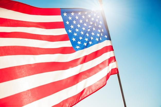 アメリカの国旗、青い空と日差しの日、7月4日。 Premium写真