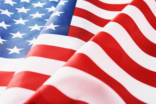 背景としてアメリカ国旗を振ってのクローズアップ。記念または独立記念日または7月4日の概念 Premium写真