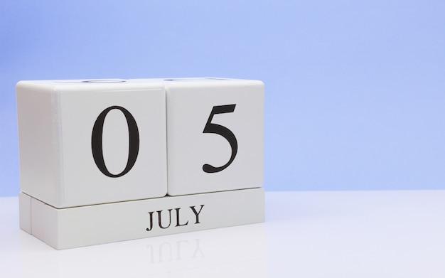 7月5日月の5日目、明るい青の背景と、反射と白いテーブルに毎日のカレンダー Premium写真