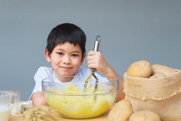 7 years boy making mashed potatoes happily Free Photo
