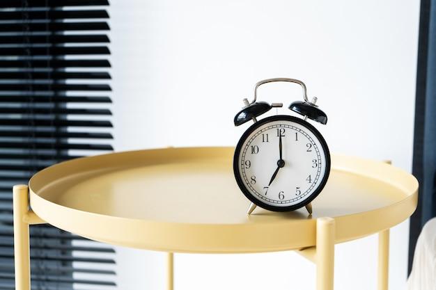 ベル付きのスタイリッシュな目覚まし時計。手は7時間を示しています。起床時間 Premium写真