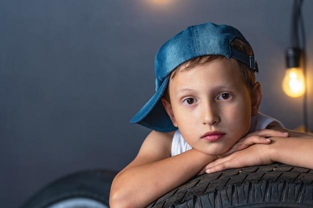 Портрет серьезного мальчика 7 лет, лежащего на шине автомобиля в гараже Premium Фотографии
