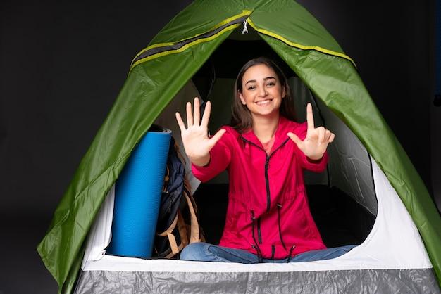 指で7を数えるキャンプの緑のテントの中の若い女性 Premium写真