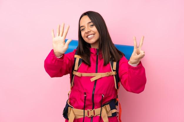 指で7を数える孤立したピンクの壁に大きなバックパックを持つ若い登山家女性 Premium写真
