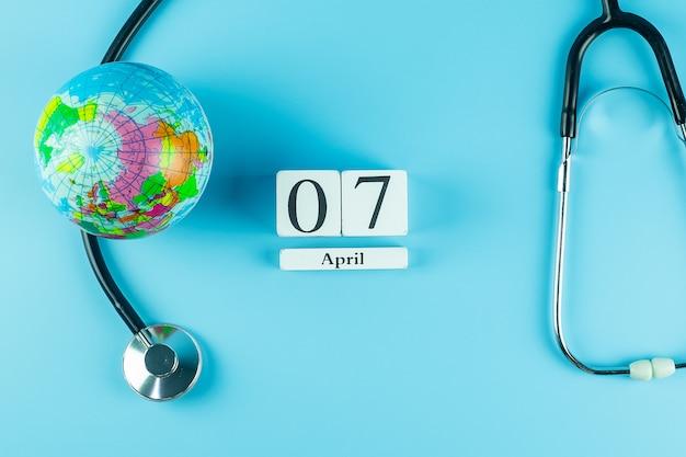 Вид сверху стетоскопа глобус и 7 апреля календарь. всемирный день здоровья Premium Фотографии