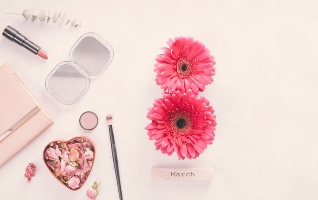 8 march inscription from gerbera flowers with cosmetics on table Free Photo