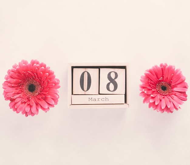 8 march inscription on wooden blocks with flowers on table Free Photo
