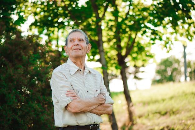 夏の公園でポーズをとって80歳の男。 Premium写真