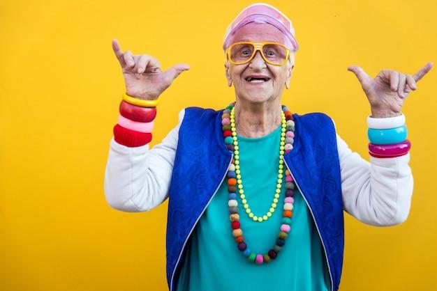 面白い祖母の肖像画。 80年代スタイルの服。色付きの背景にトラップスターダンス。年功序列と高齢者についての概念 Premium写真