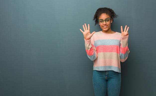 番号8を示す青い目を持つ若いアフリカ系アメリカ人少女 Premium写真