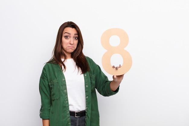 Грустный, подавленный, несчастный, держит номер 8. Premium Фотографии