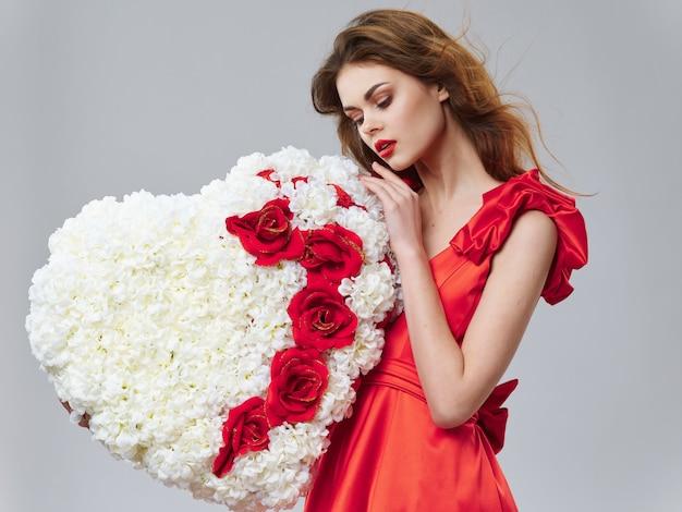 Женщина в красивом платье с цветами на 8 марта, подарки цветы на светлом фоне ко дню святого валентина студия Premium Фотографии