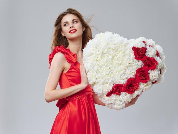 Женщина в красивом платье с цветами на 8 марта, подарки цветы на светлом фоне ко дню святого валентина Premium Фотографии
