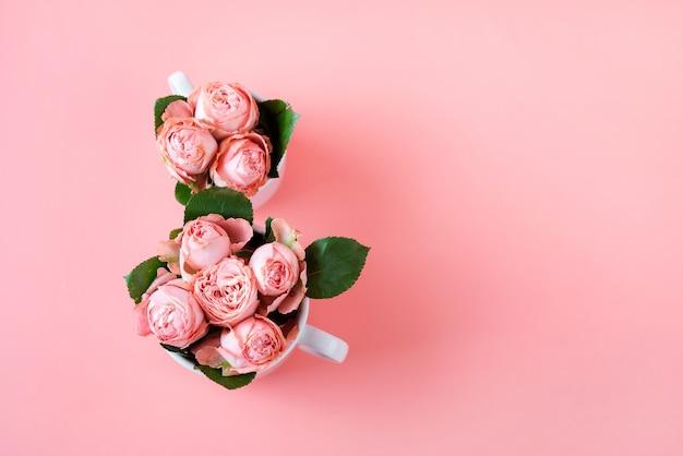 Вид сверху с двумя чашками кофе с розовыми цветами копии пространства. фон для женского дня 8 марта. Premium Фотографии