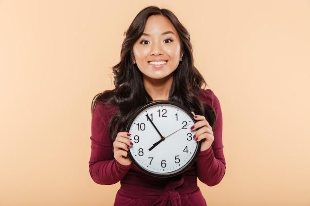桃の背景の上に楽しい何かを待っているほぼ8を示す時計を保持している巻き毛の長い髪を持つアジアの女性の幸せな感情 無料写真