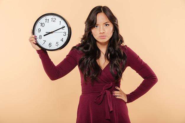 Взрослая дама с вьющимися длинными волосами держит часы со временем после 8, показывая гнев с выражением лица, положив руку на талию на бежевом фоне Бесплатные Фотографии