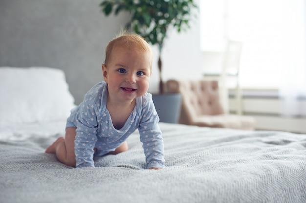 自宅のベッドの上でクロール生後8ヶ月の幸せな男の子 Premium写真