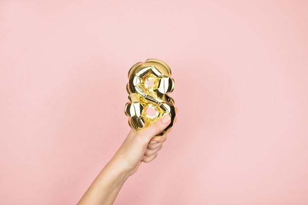 Золотая фольга раздувает цифру 8 в женской руке на розовой поверхности. счастливый женский день Premium Фотографии
