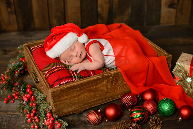 クリスマスのスーツで生後8日の小さな新生児の女の子 Premium写真