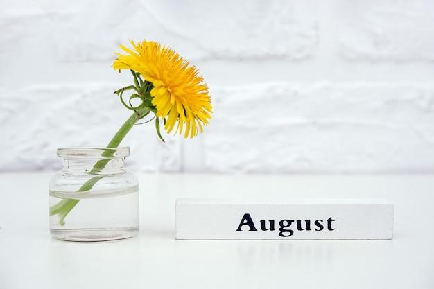 木のカレンダー夏月8月とテーブルの上の瓶花瓶に黄色のタンポポ Premium写真