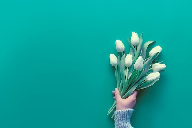 Женщина рука держать букет из белых тюльпанов, мята зеленая бумага. весна плоская планировка, вид сверху с копией пространства, пространство для текста. день матери, международный женский день 8 марта, день рождения, юбилей приветствие фон. Premium Фотографии