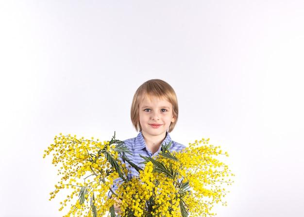Милый маленький мальчик держит букет желтой мимозы. подарок для мамы. поздравления с 8 марта, днем матери. Premium Фотографии