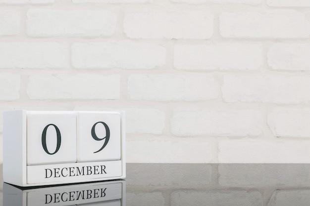 黒いガラスのテーブルと白いレンガの壁に黒9 12月の言葉でクローズアップ白い木製カレンダー Premium写真