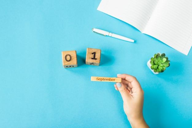 女性の手は9月1日の日付で木製のカレンダーを握ります Premium写真