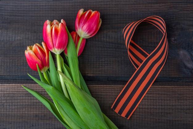 9 мая фон - красные тюльпаны, георгиевская ленточка на деревянном фоне. день победы или день защитника отечества концепции. вид сверху, скопируйте пространство для текста Premium Фотографии