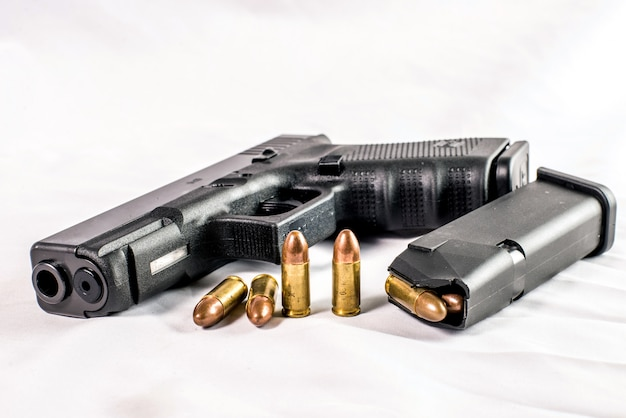 9 mm pistol gun and bullets strewn with ammunition on wooden background Premium Photo
