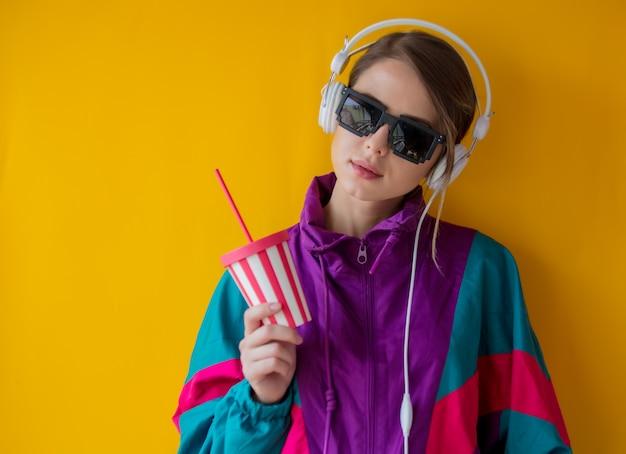 Молодая женщина в стиле 90-х годов с чашкой и наушниками Premium Фотографии