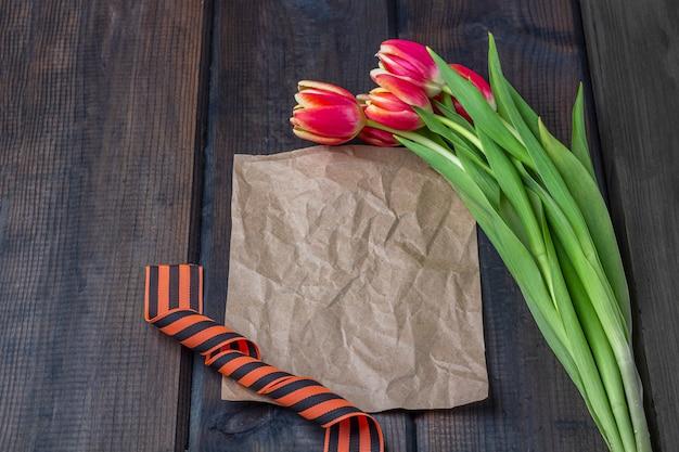 9 мая фон - шаблон пустой поздравительной открытки с красными тюльпанами, георгиевская лента и бумажные записки на деревянном фоне. день победы или день защитника отечества концепции. вид сверху, скопируйте пространство для текста Premium Фотографии