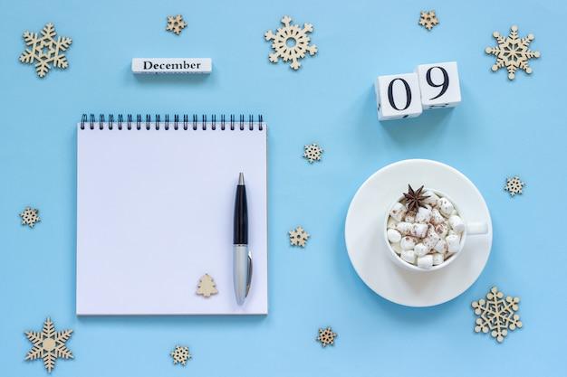 Календарь 9 декабря чашка какао и зефира, пустой открытый блокнот Premium Фотографии